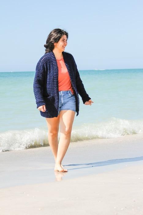 Woman wearing an easy crochet cardigan she made walking on the beach.