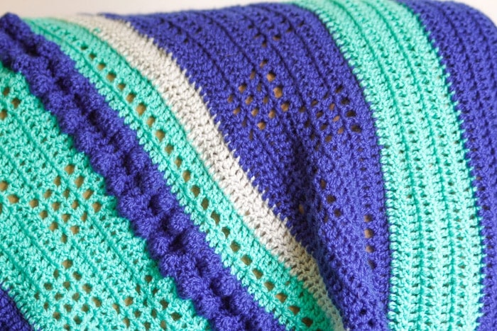 Closeup of a textured crochet lap blanket pattern in green, blue and gray stripes.