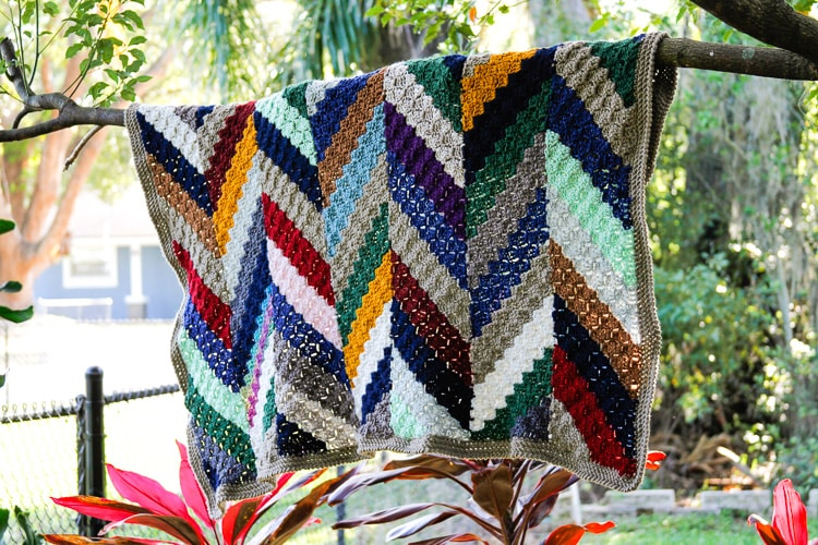 A colorful crochet scrap blanket pattern using colorful herringbone stripes hanging on a tree branch.