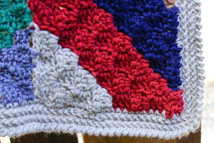 Closeup of the crochet herringbone stitch border on a crochet scrap blanket.