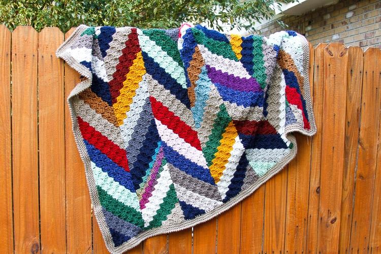 A multicolored herringbone c2c crochet scrap blanket hanging on a wooden fence.