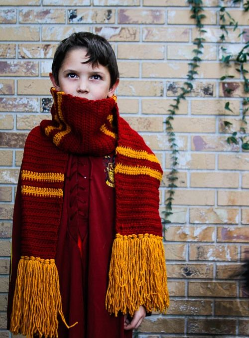 Young boy wearing a Harry Potter Crochet scarf in red and gold gryffindor colors.