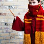 Boy wearing a Gryffindor crochet scarf and waving a wand in front of a brick wall.