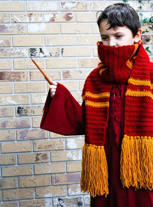 Young boy wearing a Gryffindor House Crochet scarf and waving a wand.