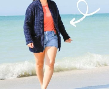 woman wearing blue crochet cardigan on a beach