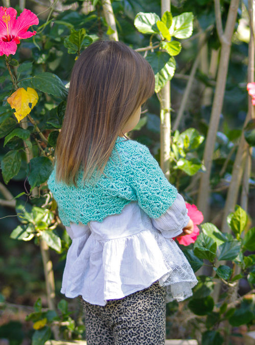 Girl wearing a crochet shrug in front of a hibiscus plant.