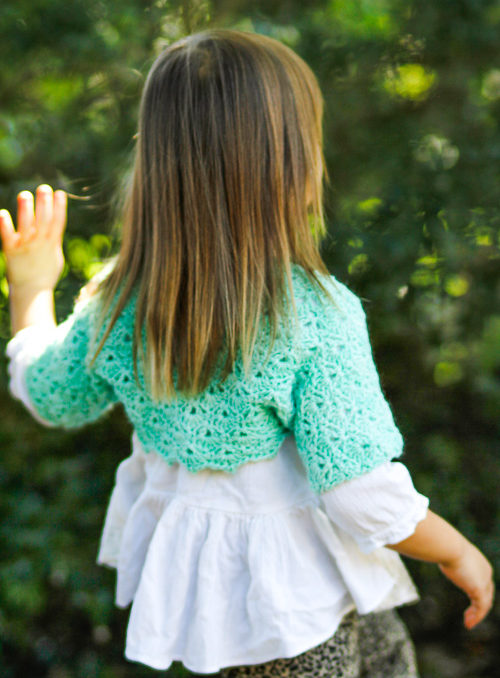 A 5 year old girl walking towards some green trees wearing a crochet bolero.
