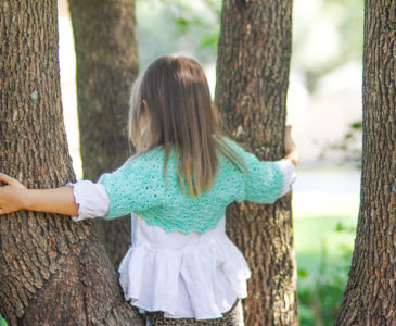 Young girl wearing a green bolero and a white ruffled shirt standing in some trees.