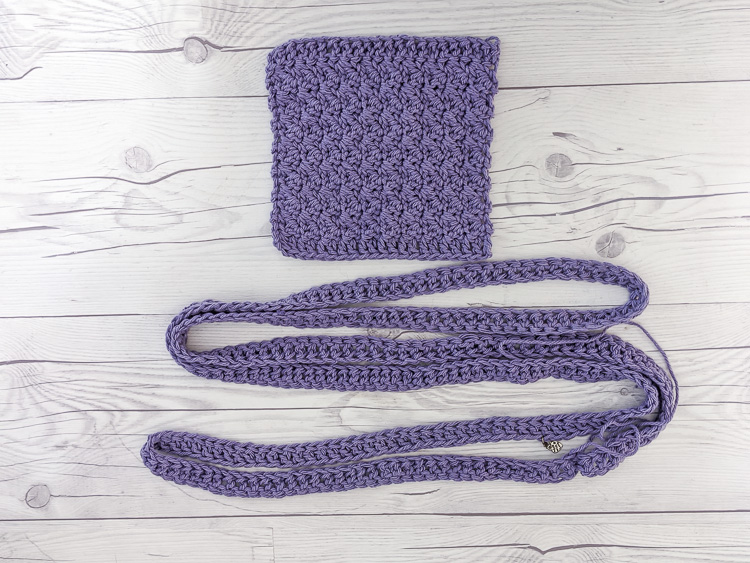 The pocket square and handle of this crocheted tote bag pattern are shown laying on a white table.