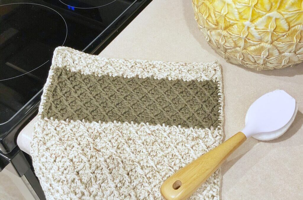 Textured crochet dishcloth on a counter with a spoon