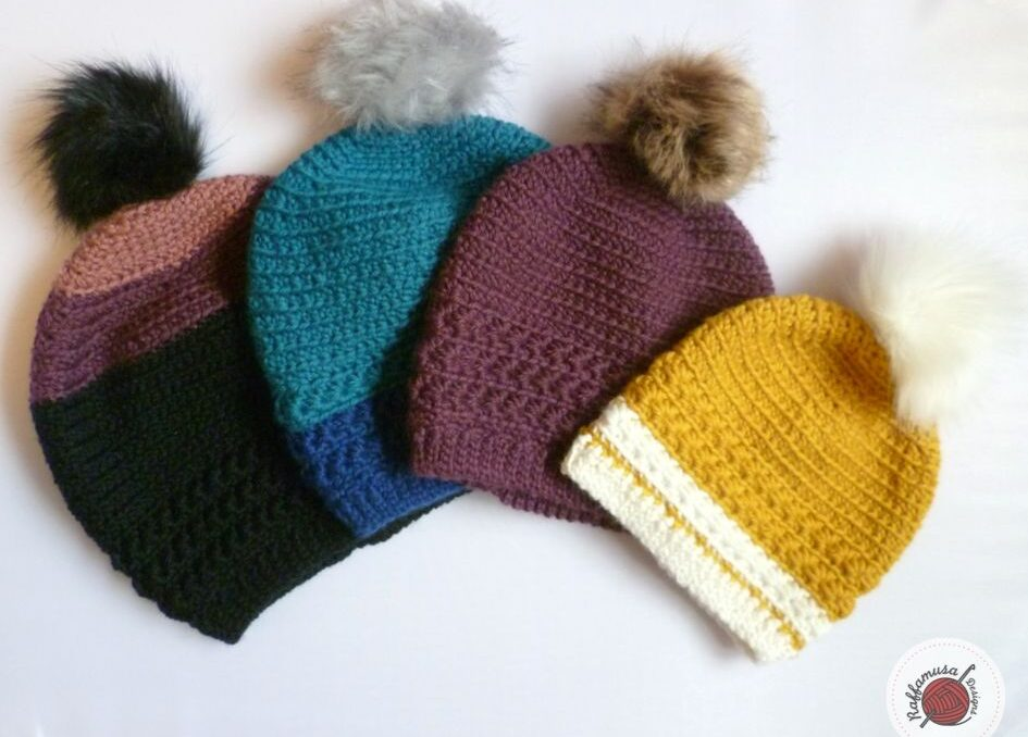 Four crochet beanie hats  with pompoms in various colors laid in a row.