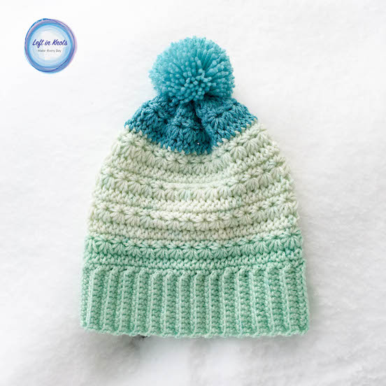 A striped crochet star stitch beanie with a pom pom.