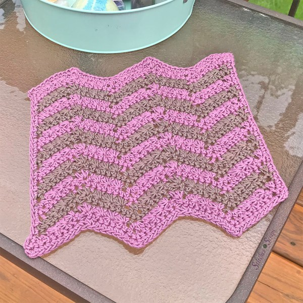 A pink and brown crochet chevron dishcloth on a glass table.