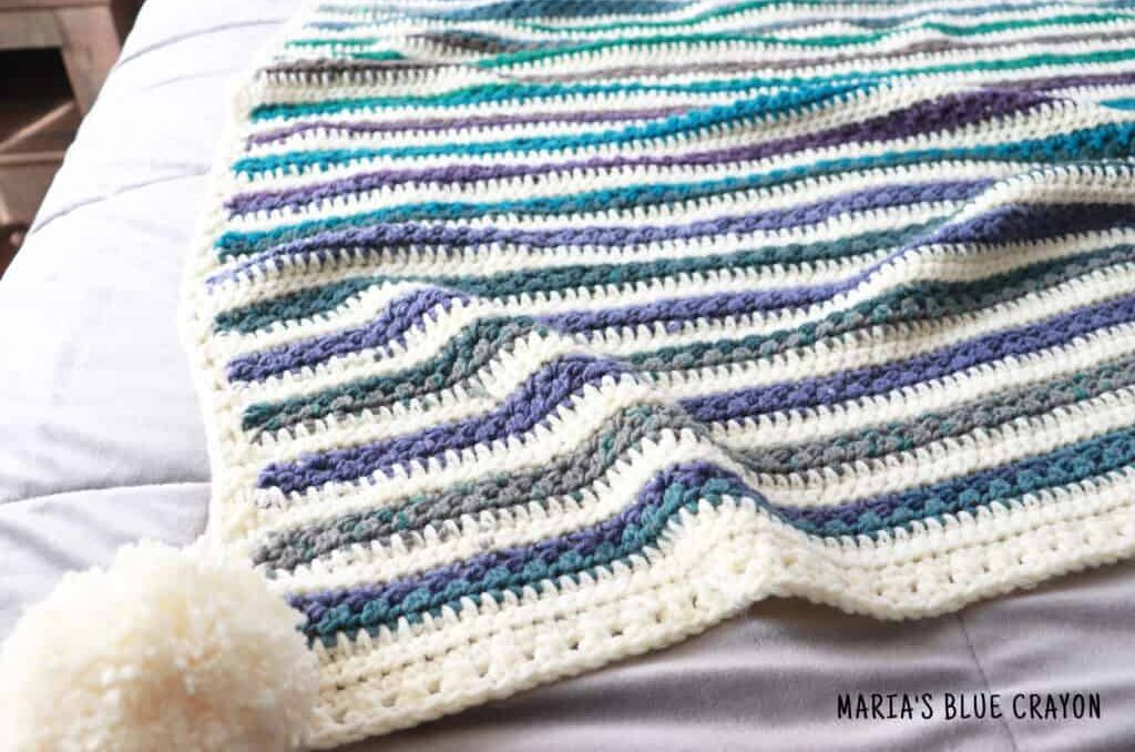 Close up photo of a striped crochet blanket with a pom pom decoration.