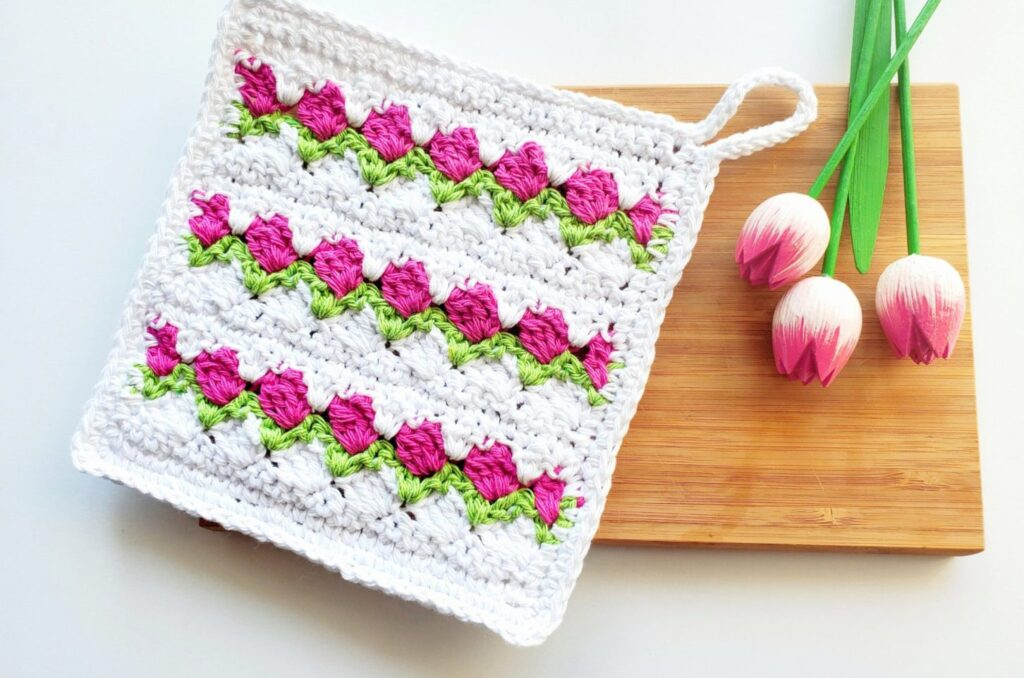 crochet tulip stitch dishcloth on a board with tulips