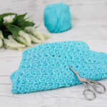 A crochet star stitch dishcloth with yarn and scissors.