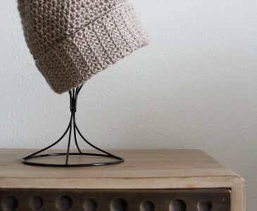 A tan hat with a folded up brim displayed on a hat holder
