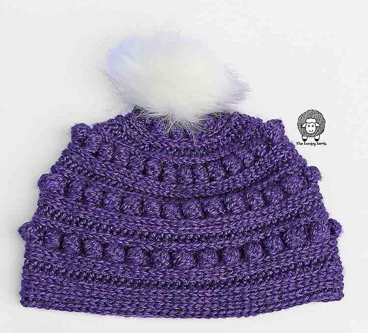 A purple bobble stitch crochet beanie with a white pompom.