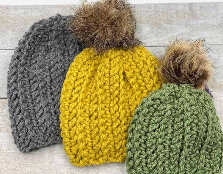 3 colorful crochet beanies stacked in a row on a wood table
