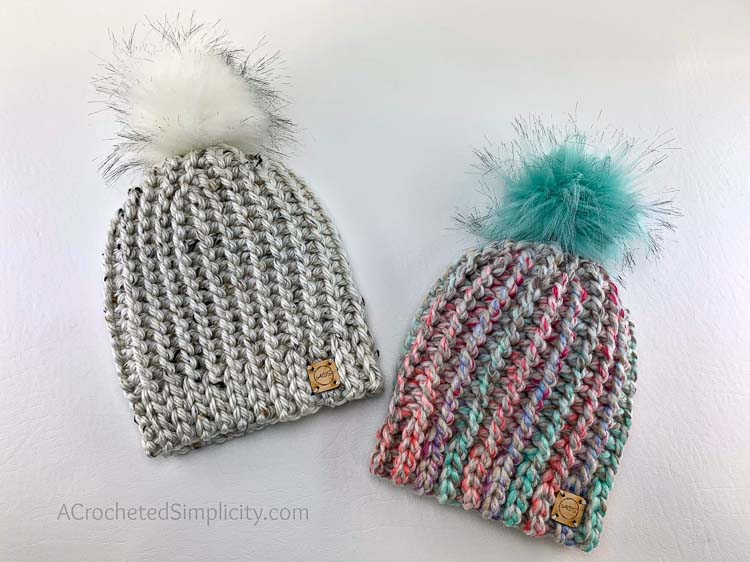Two chunky yarn crochet hats with pom pom toppers.