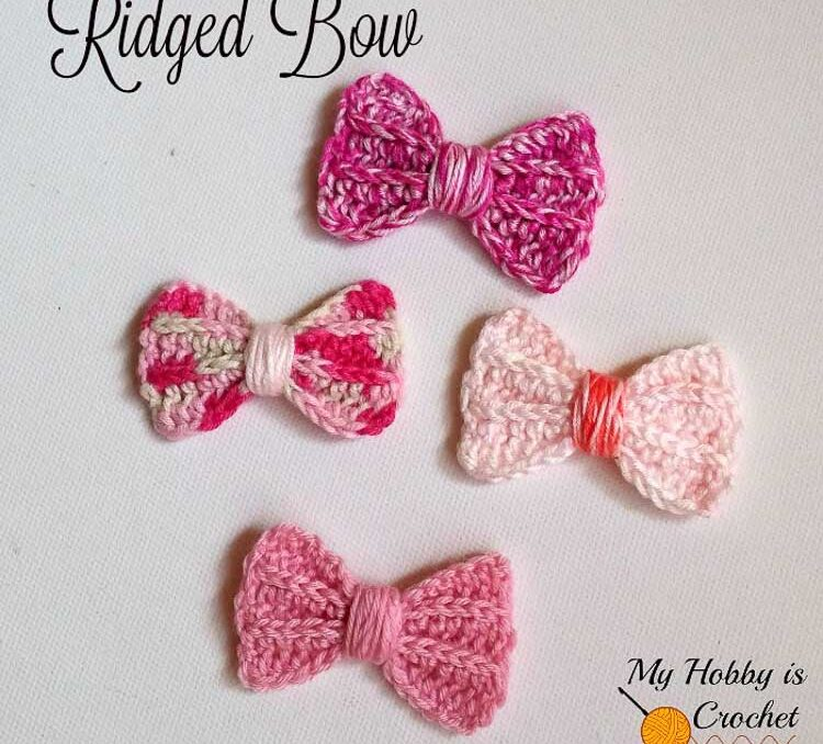 Four crochet bows in shades of bright pink on a table.