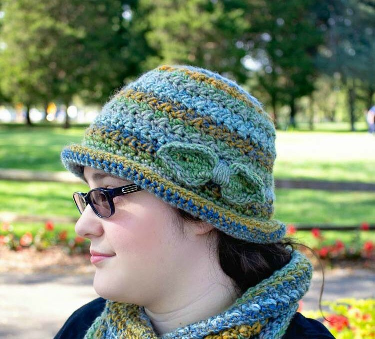 A colorful crochet cloche hat worn by a woman in a park