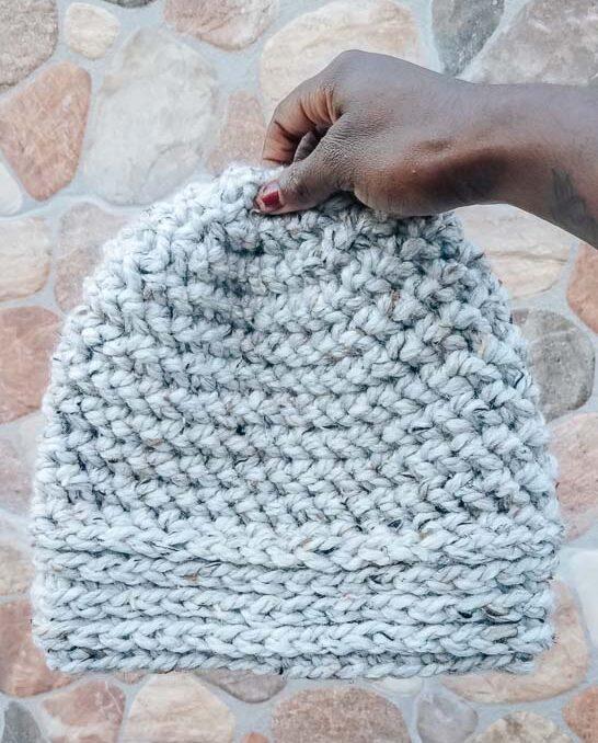 A chunky crochet beanie before a stone wall