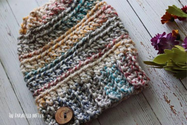 A colorful crochet cowl on a table with flowers