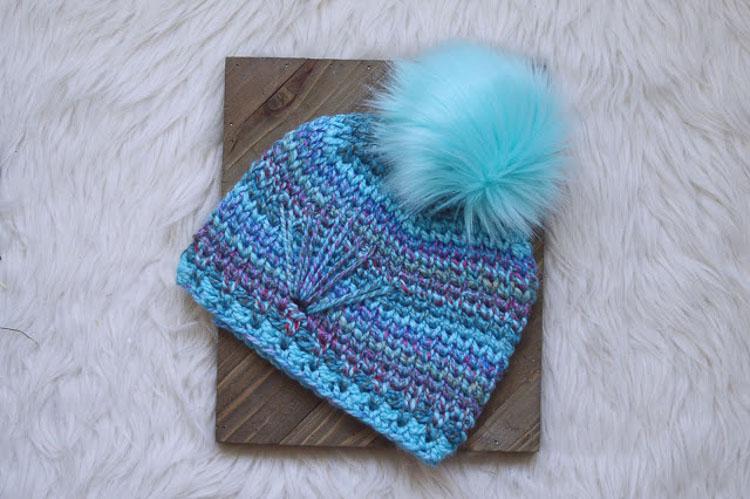 Blue striped crochet beanie with a pom pom on a white furry blanket