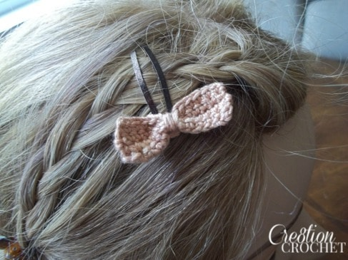 Closeup photo of a girl wearing a pink crochet bow on a barette.