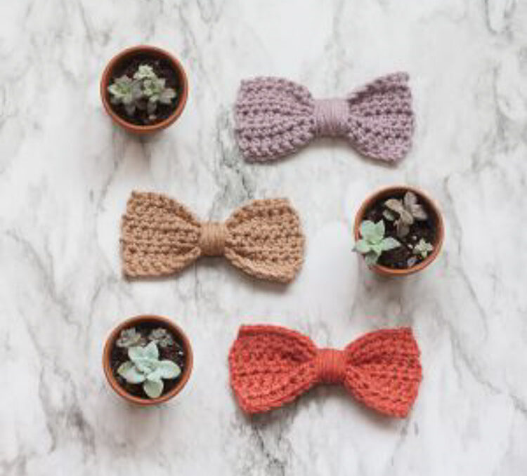 Three little crocheted bows on a table with succulents