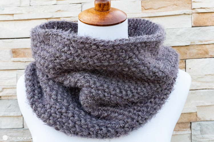 A gray crochet cowl made with Red Heart Hygge Yarn on a white mannequin