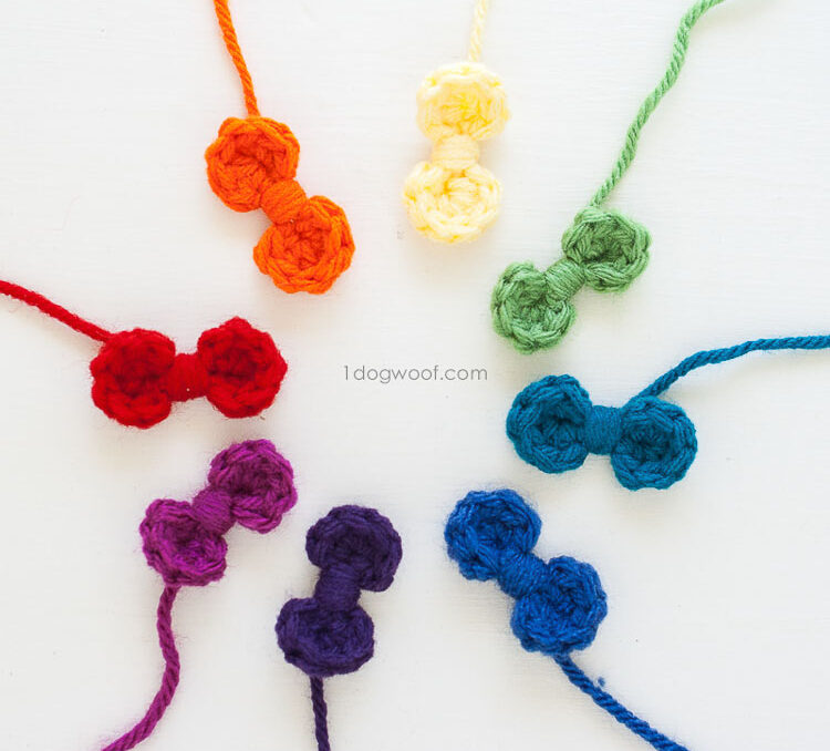Crochet bows made from scrap yarn arranged in a circle of rainbow colors.
