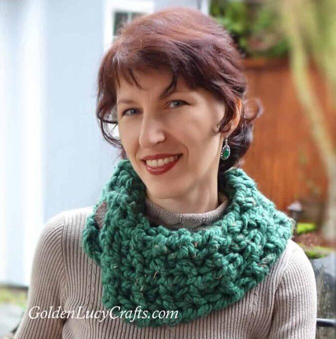 Wearing a chunky green crocheted cowl over a turtleneck sweater