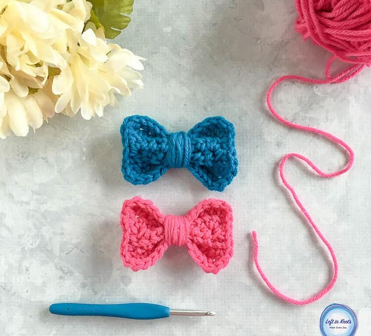 A blue and pink crochet bow with a crochet hook
