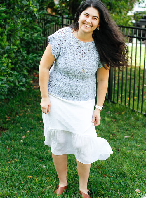 woman wearing a blue lace crochet tee and a white skirt