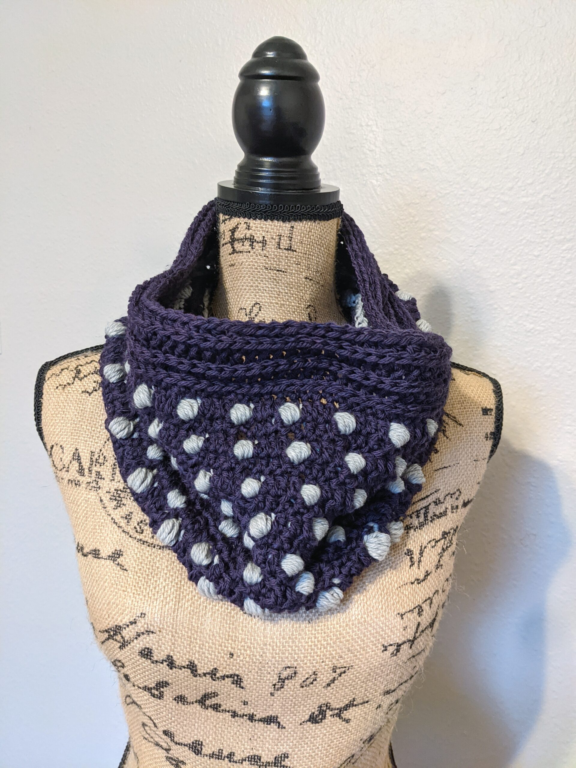 A cowl with crochet puff stitch polka dots on a mannequin