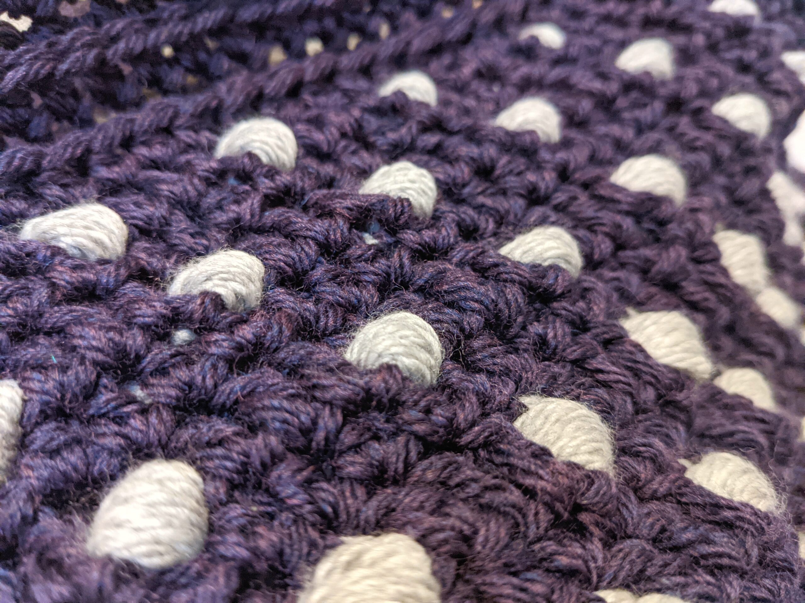 A close up of crochet puff stitches in gray yarn on a purple crochet background