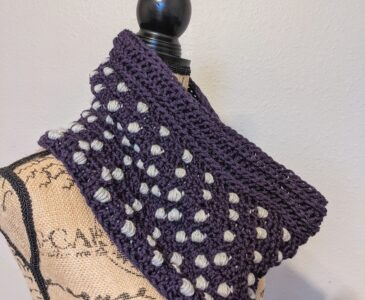 Side view of the polka dot puffs crochet cowl pattern on a mannequin