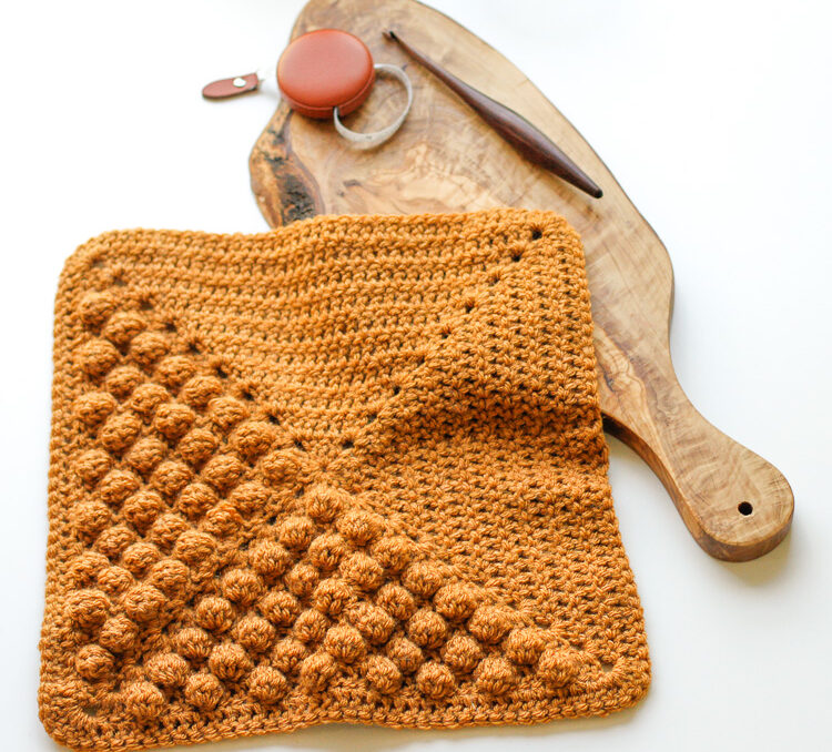 a mustard yellow crochet blanket square made with bobble stitches