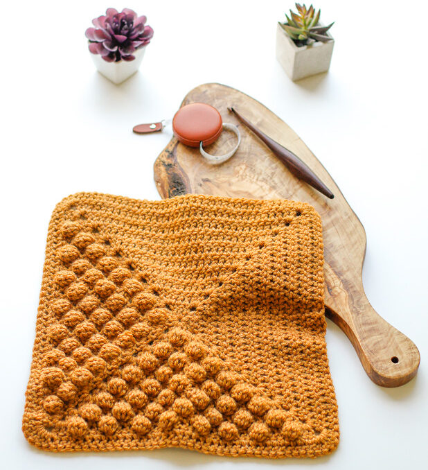 a crochet quilt block with the bobble stitch on a table with a tape measure and crochet hook.