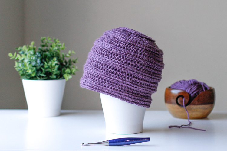 a purple crochet beanie on a table with a plant, crochet hook and yarn bowl