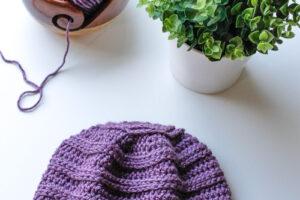Purple crochet chemo cap beanie laid flat on a white table near yarn and a plant